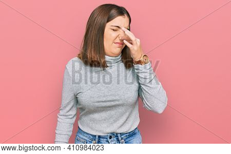 Young beautiful woman wearing casual turtleneck sweater smelling something stinky and disgusting, intolerable smell, holding breath with fingers on nose. bad smell