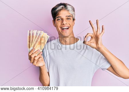 Young hispanic man holding 500 norwegian krone banknotes doing ok sign with fingers, smiling friendly gesturing excellent symbol