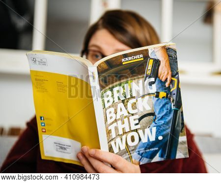 Paris, France - Mar 2, 2021: Curious Woman Reading Latest Advertising Catalogue Of Karcher German Fa