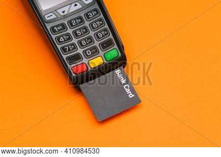 Payment Terminal With A Credit Card. Modern Device For Paying For Services And Goods On An Orange Ba