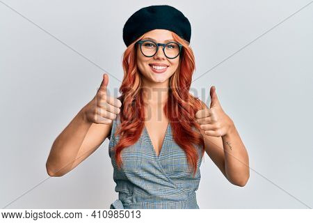 Young redhead woman wearing fashion french look with beret success sign doing positive gesture with hand, thumbs up smiling and happy. cheerful expression and winner gesture.