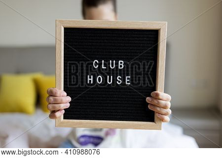 Young Caucasian Woman Board With Inscription Clubhouse. Application Clubhouse - Voice-only Social Me