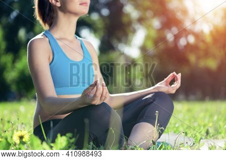 Girl Meditates In Lotus Pose On Green Grass. Practicing Of Yoga Concept. Young Woman Body In Sportsw
