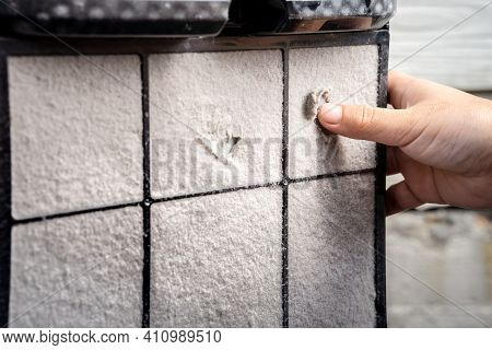 The Filter Of The Pm2.5 Air Purifier With Thick Dust Forms A Sheet. A Person's Hand Tried To Remove