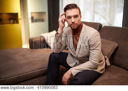 Fashionable handsome middle-aged man in elegant smart casual clothes having a rest at home. Success and well-being.