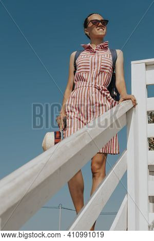 Beautiful Tanned Woman In A Beach Dress Against A Blue Sky. Portrait Of A Girl On Vacation.