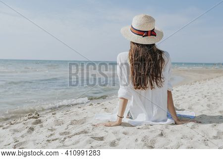 A Woman Sits On The Seashore From The Back Looks Into The Distance At The Sea.