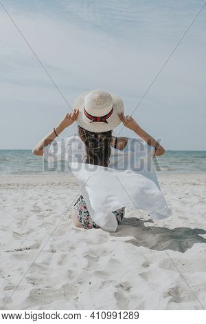 A Woman On The Seashore From The Back In Sunny Weather Sits Alone On A Sandy Beach. Summer Vacation