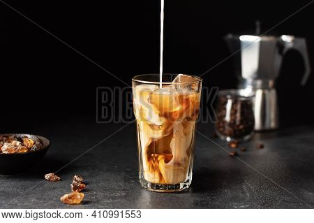 Pouring Milk Into A Glass With Iced Coffee Over Black Background. Cold Refreshment Summer Drink.
