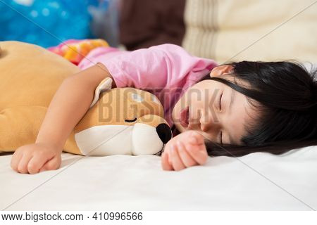 Adorable Little Girl Slept And Hugged The Dog Doll On The Soft Bed. Child Sleeping Happily. Cute Chi
