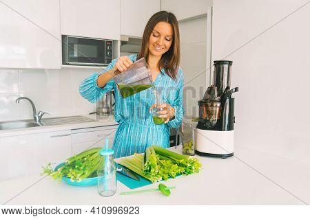 Fresh Homemade Celery Detox Juice. Healthy Young Woman Making Freshly Pressed Celery Juice In Juicer