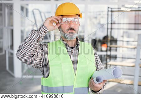 Confident Purposeful Bearded Man In Glasses And Helmet Holding Blueprints. Mature Contractor In Unif