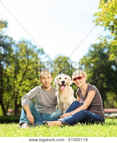 Smiling young couple hugging a labrador retreiver dog in a park, shot with a tilt and shift lens