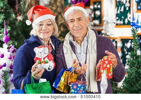 Portrait of happy senior man shopping for Christmas with woman in store