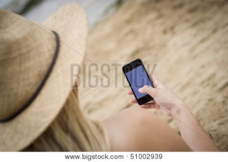 Woman Sat On The Beach Using A Mobile Phone