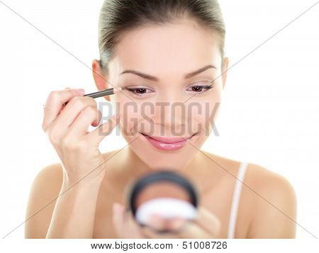 Eyeliner eye makeup beauty care woman. Asian girl putting eye pencil color on eyes looking in a pocket mirror smiling happy isolated on white background. Make up with multiracial Asian Caucasian girl.