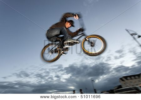 Young man performs BMX stunts during sunset at the street. Blurred motion. poster