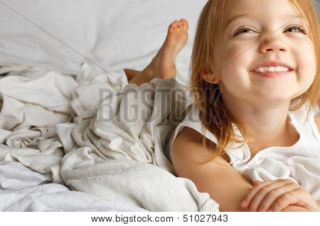 Smiling young girl in white covered bed