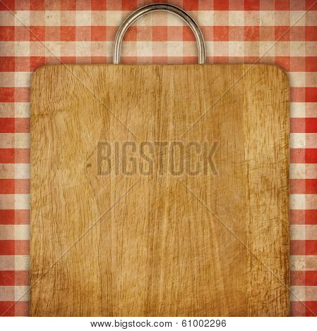 hardboard or breadboard over red checked gingham picnic tablecloth grunge background