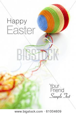 Colorful wool yarns unwraps from easter egg. Space for text isolated on solid white background