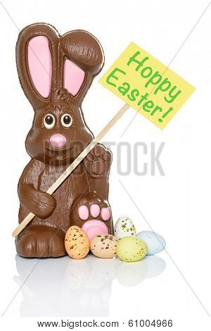 Chocolate bunny holding a sign that says Hoppy Easter, with some candy eggs at his feet. Isolated on a white background.