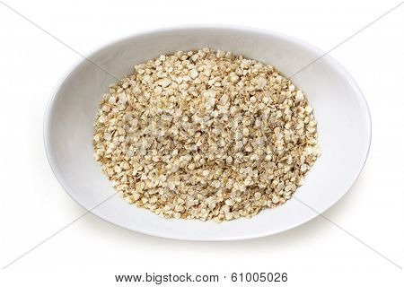 Quinoa flakes in small white  bowl, isolated.  Overhead view.