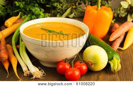 Vegetable soup surrounded by fresh vegetables.