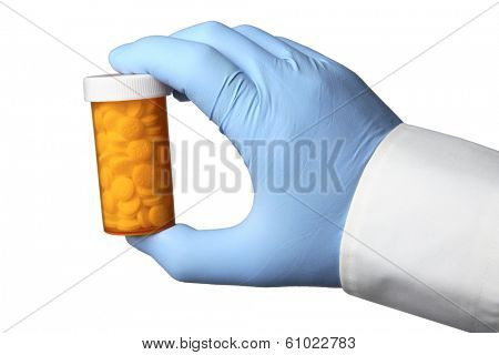 Hand with blue glove holding bottle with pills on white