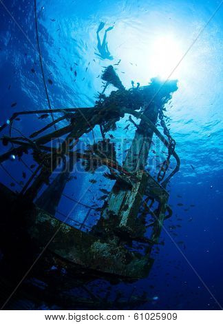 Bottom view of the ship wreck and silhouette of the snorkeler on the surface