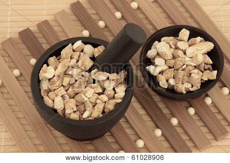 Korean ginseng chinese herbal medicine in a mortar with pestle and bowl. Panaz schinsen. Ren shen. poster