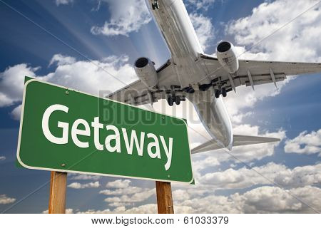 Getaway Green Road Sign and Airplane Above with Dramatic Blue Sky and Clouds.