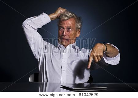 Upset Frustrated Senior Man Pointing At His Tablet