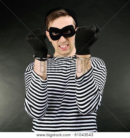 Thief with handcuffs on dark background