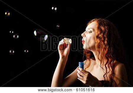Beautiful Redhead Girl Blows Bubbles. Studio Portrait, Profile View