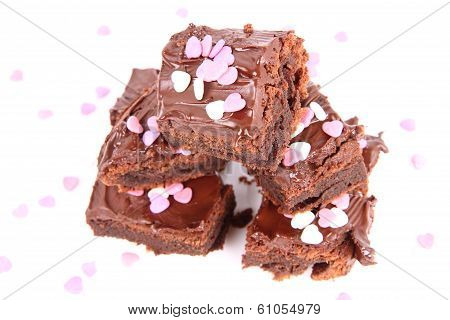 Slices of a brownie covered with chocolate and decorated with sugar hearts