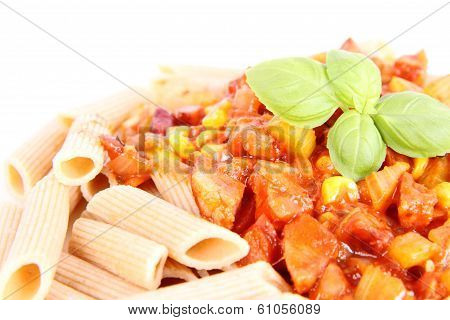 Whole grain Penne with sauce decorated with basil