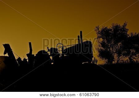 Silhouette of Old Tractor and Combine