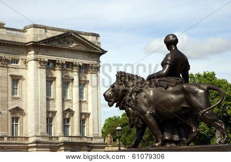 A Bronze Woman Statue Standing Next To A Lion Statue