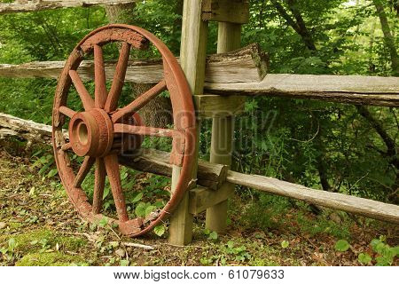 A Rustic Old Wooden Wheel Against A Fence