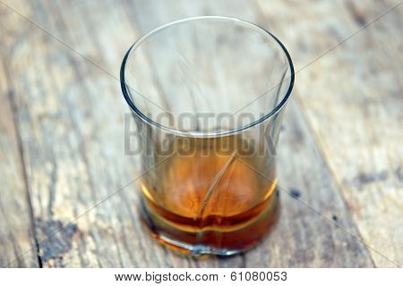 A Single Glass Of Scotch On A Wooden Table