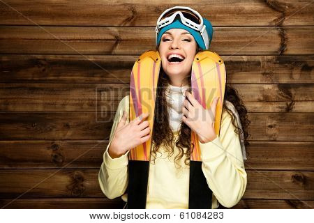 Smiling woman with skis standing against wooden house wall