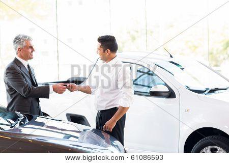 senior car salesman handing over new car key to customer at showroom
