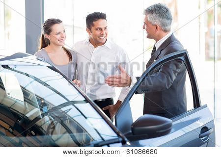 mature salesman showing new car to a couple in showroom
