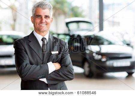 confident senior car dealer principal standing in showroom