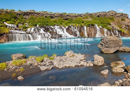 Hraunfossar is a very beautiful Icelandic waterfall in the west of the island. It comes from the lava field and pours into the Hvita river with a incredibly blue water. Long exposure. poster