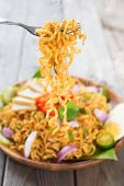 Spicy fried curry instant noodles or Malaysian style maggi goreng mamak.  Ready to serve on wooden dining table setting. Fresh hot with steamed smoke. poster