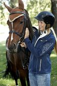 Female rider in equestrian helmet caressing horse, smiling. poster