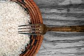 Rice and fork on wooden background texture poster