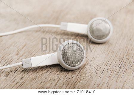 Modern Portable Audio Earphones On Wood