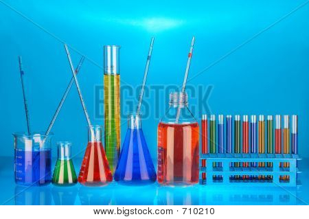many different coloured chemical solutions in laboratory glasses with pipettes on blue background poster